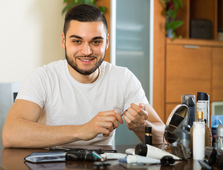metrosexual: Smiling metrosexual guy doing manicure at home