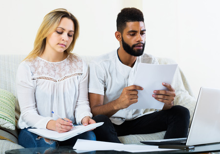 interracial family: Interracial family filling papers for mortgage indoors