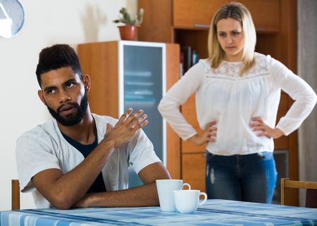 portrait couple: Upset black man and frustrated white housewife having bad quarrel