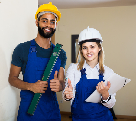 constructor: Constructor and happy professional builder with spirit level at site Stock Photo
