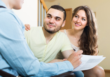 Young couple discussing details of private insurance with agent 版權商用圖片