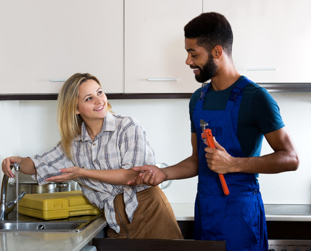 thanking: Attractive woman thanking black professional plumber for work. Focus on the woman