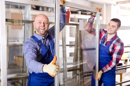 glasswear: workmen with windows production at modern factory