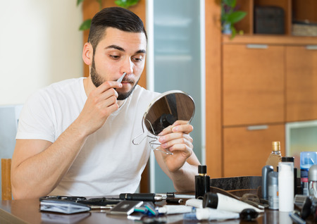 20 years old: Guy 20 years old remove hair from his nose and ears with trimmer Stock Photo
