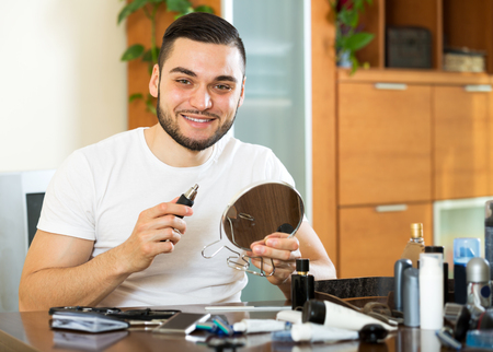 trims: Happy beautiful guy trims nose and ears hair at home