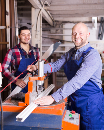 toolroom: Couple of young workers near milling machine at factory Stock Photo