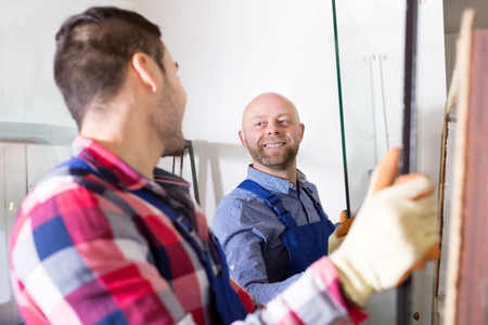 Two workers working with glass for windows at workshop Stock Photo