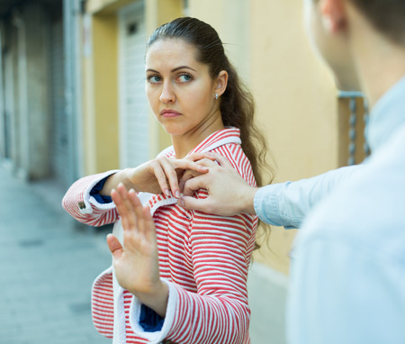 Young couple 25s having bad quarrel on city street in spring day Stock Photo