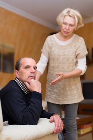 flatter: Worried mature woman assuaging man of anger indoors. Focus on man Stock Photo