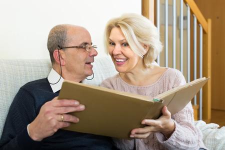spouses: Portrait of smiling senior mature spouses with picture album indoors