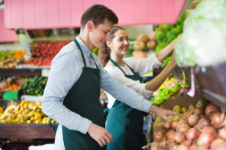 displays: Friendly smiling sellers having vegetables and fruits on displays of market Stock Photo