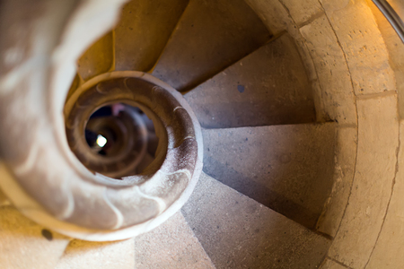backstairs: Close up view at narrow stone spiral stairway indoors Stock Photo