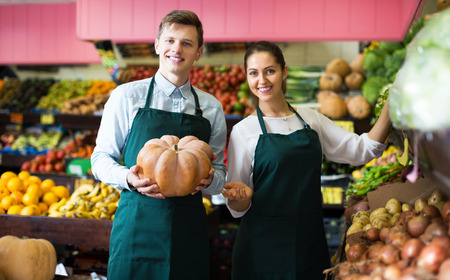 thanksgiving adult: Two positive stuff in apron selling sweet pumpkin at marketplace. Focus on man