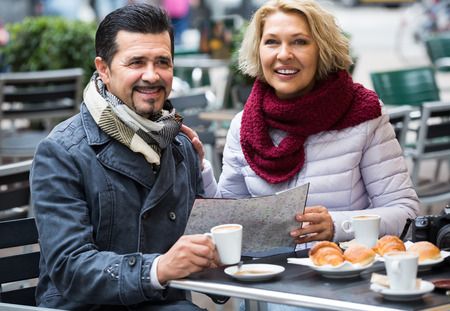 gente adulta: Turistas americanos feliz mayor tomando un café en el café y la lectura de mapa Foto de archivo