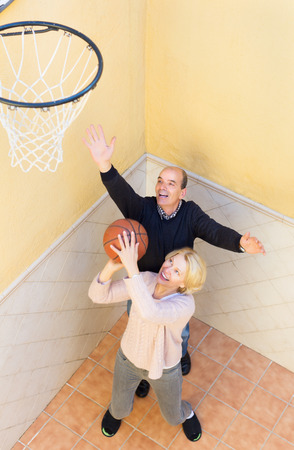 spouses: Happy activity senior spouses throwing the ball into basket