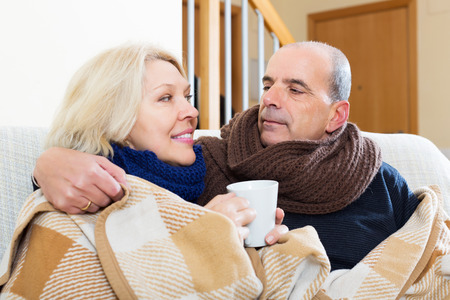 spouses: Mature positive spouses under blanket drinking tea on couch