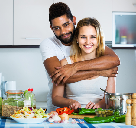 interracial couple: Young happy interracial couple cooking vegetables and laughing
