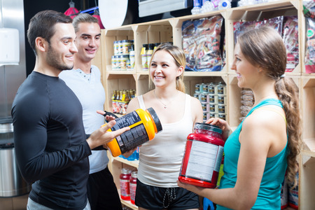 Portrait of active people with sport nutrition products in shop Stock Photo