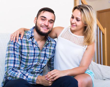 amigos abrazandose: Retrato de mujer joven sonriente y un hombre sentado en el sof� Foto de archivo