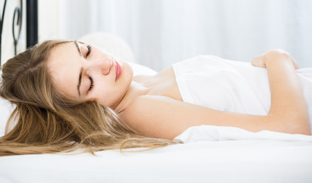 drowse: Young american woman lying in bed under sheet with closed eyes Stock Photo