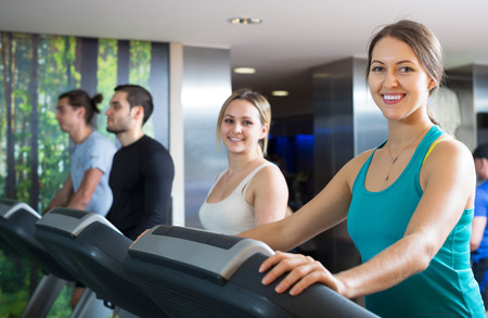 russian man: Smiling group of young adults training on treadmills in gym Stock Photo