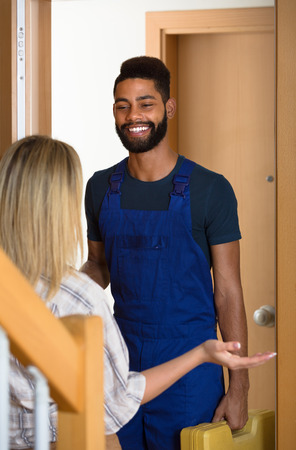 blue overall: White girl meeting smiling African handyman in blue overall at the doorway