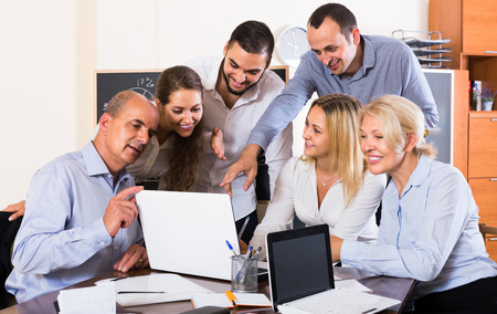 spanish looking: positive spanish colleagues looking at laptop and smiling