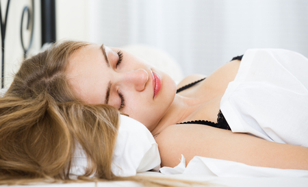 drowse: Portrait of charming young woman with long hair sleeping in bedroom Stock Photo