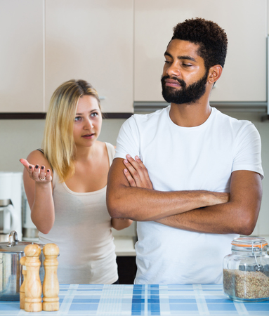 interracial family: Young unhappy interracial family couple with serious faces quarrelling in kitchen. focus on man