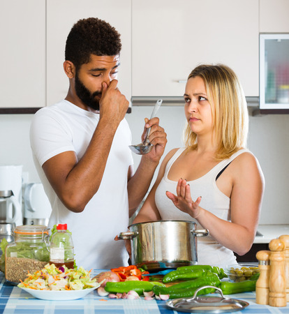 stinking: Portrait of young interracial couple with stinking food in home kitchen