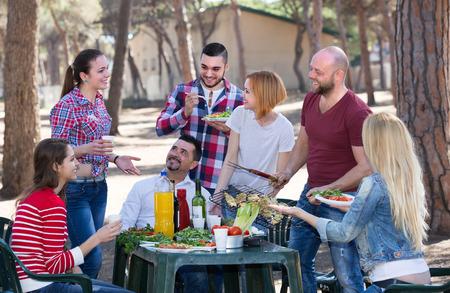 llamas de fuego: Positive colleagues making grill at summer corporate party outdoors. Selective focus Foto de archivo