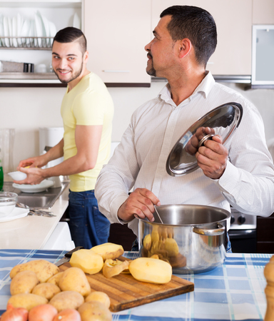 russian man: Adult father and son cooking potato soup indoors