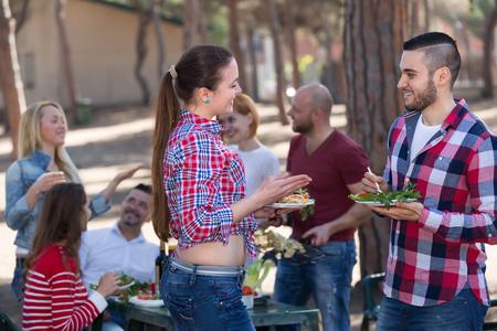 llamas de fuego: Adultos j�venes positivos que hacen de la parrilla en la fiesta corporativa verano al aire libre. Enfoque selectivo
