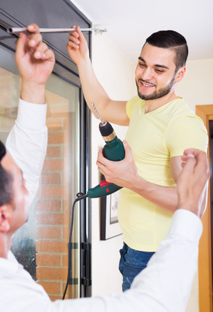 corbel: Two male young putting corbel at residential kitchen Stock Photo