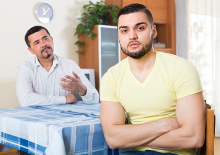 russian man: Two serious adult guys having conflict indoors