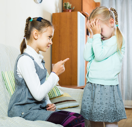 shaming: Serious girl lecturing little sister in domestic interior
