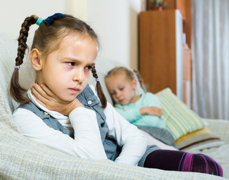 Offended little girl sitting apart of younger sister after argue at home Stock Photo - 50121634
