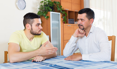 swear: Two despair male adults arguing about something in living room