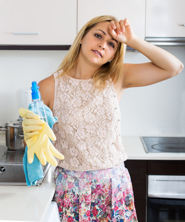 kitchen furniture: Tired young housewife cleaning furniture in kitchen