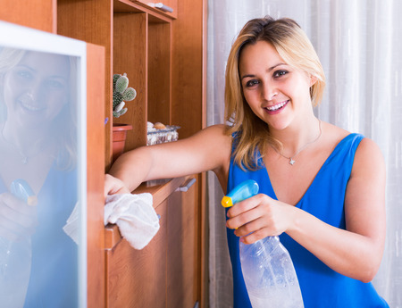 spanish woman: adult spanish woman in casual cleaning at home and smiling