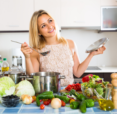onion: Muchacha sonriente feliz preparar comida saludable con verduras en el hogar