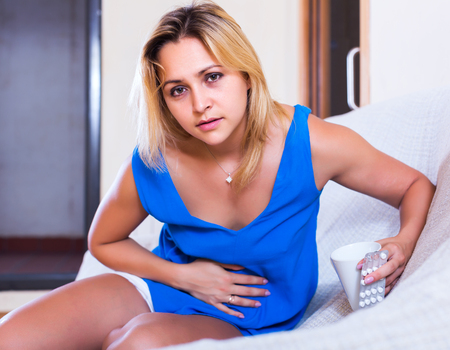 pancreatitis: Portrait of blonde young girl with abdominal pains in home interior