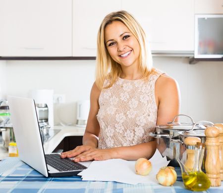 advantaged: blonde female signing documents at the kitchen Stock Photo