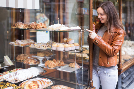pastila: Portrait of happy adult brunette looking at fancy cakes in bakery Stock Photo