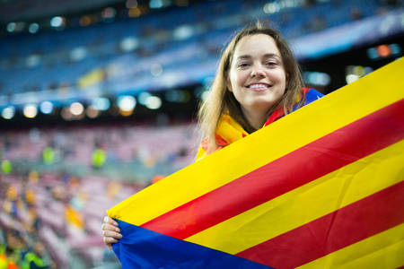 fandom: positive female football fan with flag of Catalonia at stadium