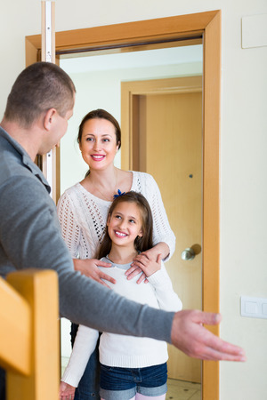 Man standing at doorway and inviting guests to come inside. Focus on girl Stock Photo