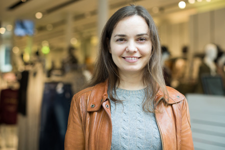 Portrait of cheerful smiling young woman in European apparel store