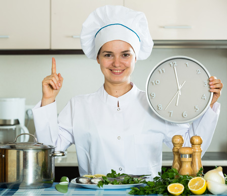 cartilaginous: Happy young cook preparing atlantic fish and checking time Stock Photo