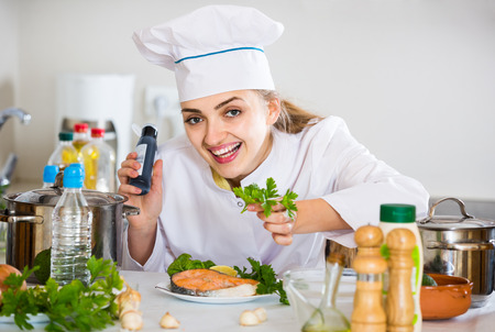 kitchen spanish: Happy young spanish cook with prepared salmon in professional kitchen