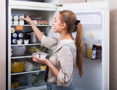 refrigerador: Feliz mujer joven de pelo largo organizar los productos en los estantes de nevera y sonriente